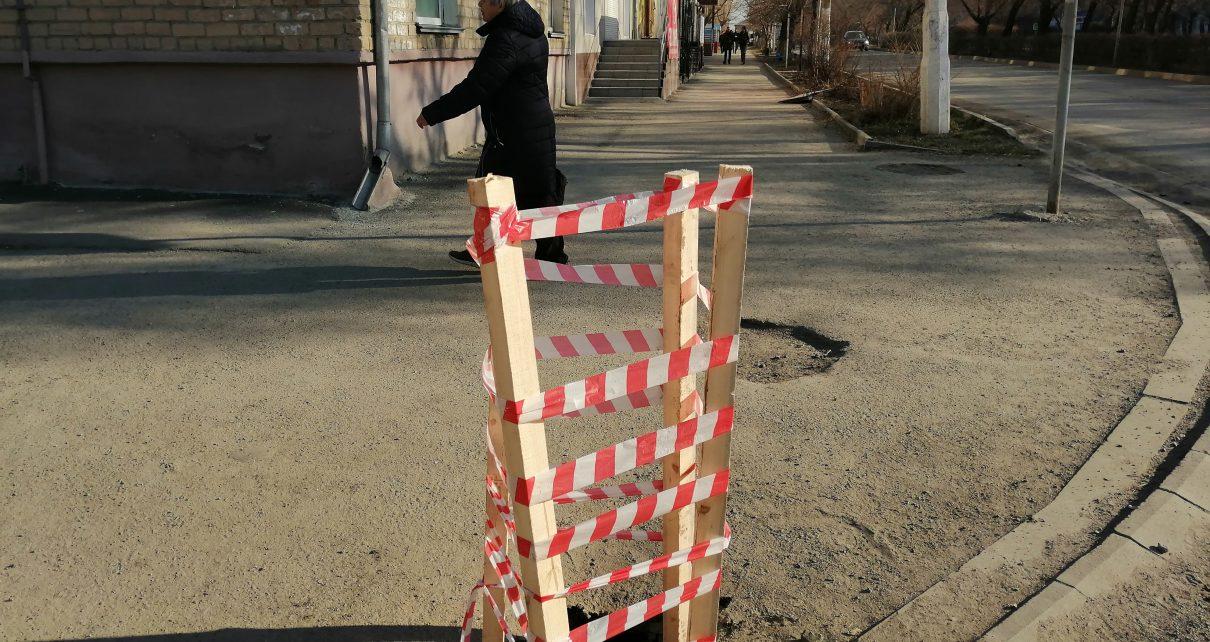 Образовавшийся провал асфальта на тротуаре обозначили сигнальной лентой